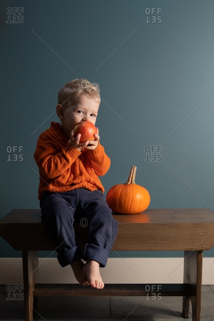 Blonde little boy sitting on bench beside a pumpkin eating an apple