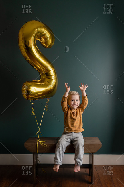 """Little boy holding his arms in the air while sitting on wooden bench beside a large gold """"2"""" birthday balloon"""