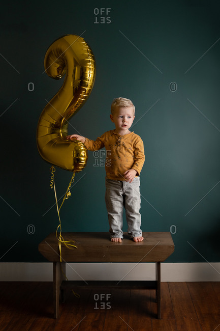 """Little boy standing on a wooden bench beside a large gold """"2"""" birthday balloon"""