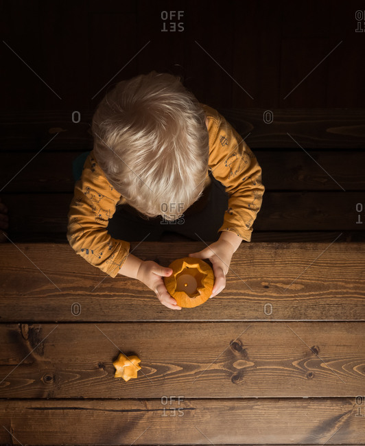 Overhead view of a little boy looking into a small pumpkin with tealight candle