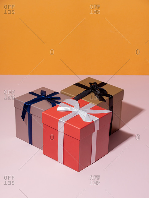 Three holiday boxes on a pink table and yellow background