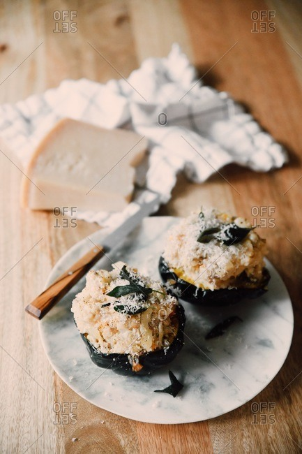Roasted eggplant topped with parmesan cheese plate with knife on wooden surface