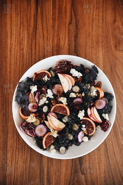 Purple kale and fruit salad on wooden table