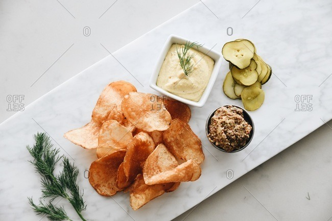 Overhead view of chips and pickles with dip on marble surface