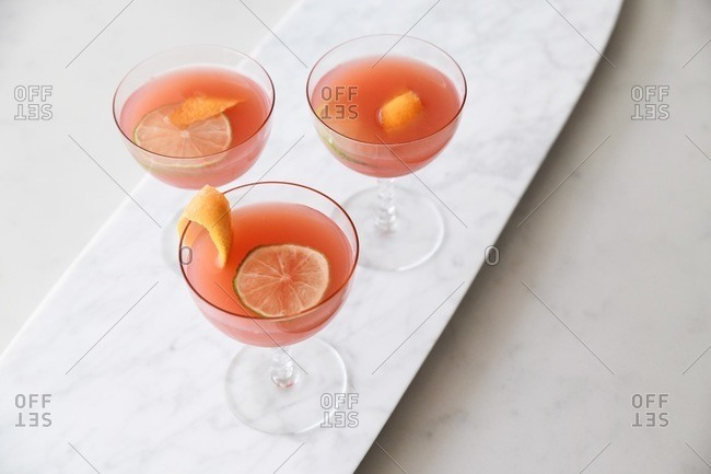 Overhead view of three pink fruity cocktails in coupe glasses