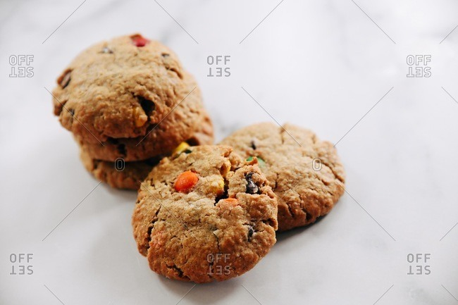 Cookies with chocolate chips and candy pieces on a marble surface