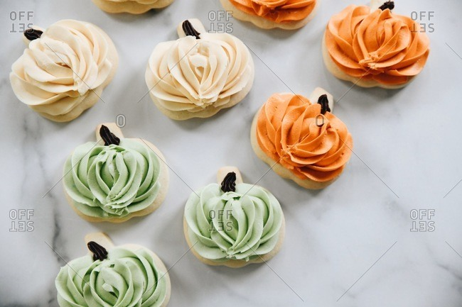 Pumpkin shaped autumn cookies with icing on a marble surface