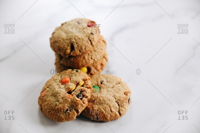A stack of cookies with chocolate chips and candy pieces on a marble surface