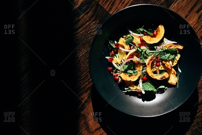 Salad of squash, onion and pomegranate in a black bowl on wooden table