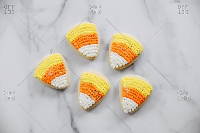 Sugar cookies decorated as candy corn on a marble surface