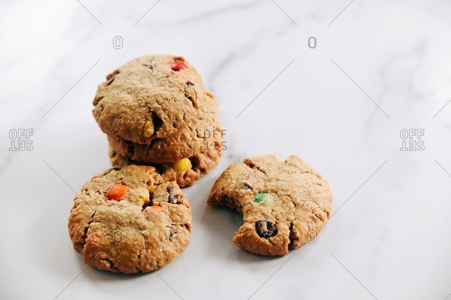 Top down view of cookies with chocolate chips and candy pieces on a marble surface