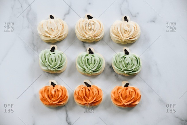 Green, white and orange pumpkin shaped sugar cookies with icing on a marble surface
