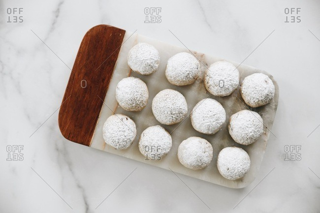 Overhead view of cookie dough balls sprinkled with powdered sugar on marble surface