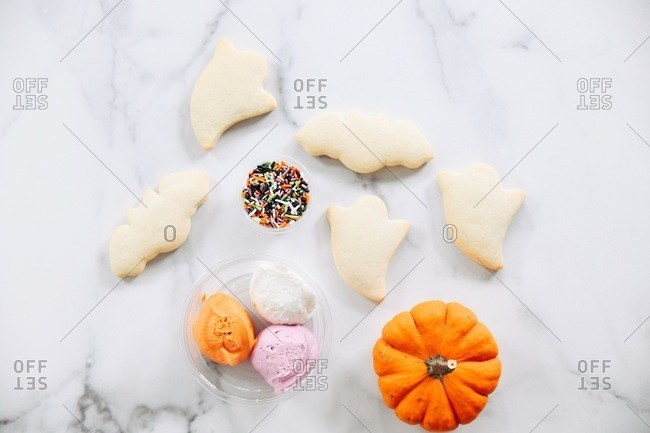 Ghost and bat shaped Halloween sugar cookies beside icing and sprinkles on a marble surface with a pumpkin