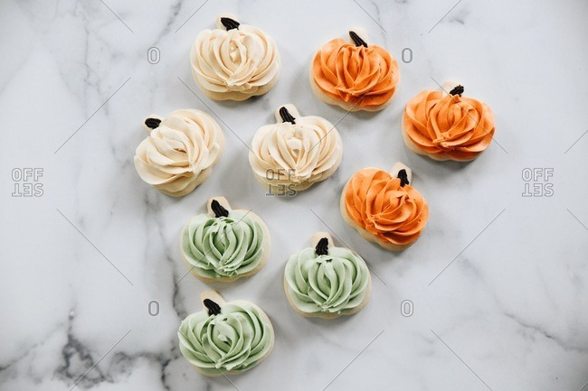 Top view of pumpkin shaped autumn cookies with icing on a marble surface