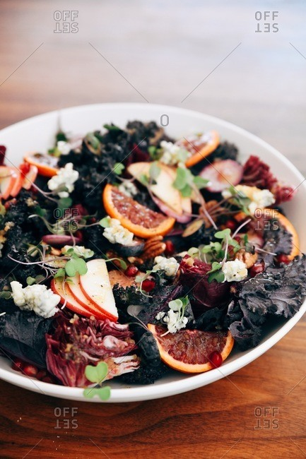 Close up of a purple kale and fruit salad on wooden table