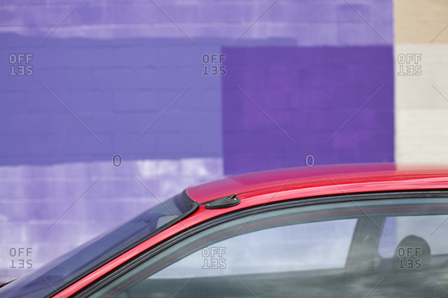 Building exterior, painted wall, purple painted blocks and red car.