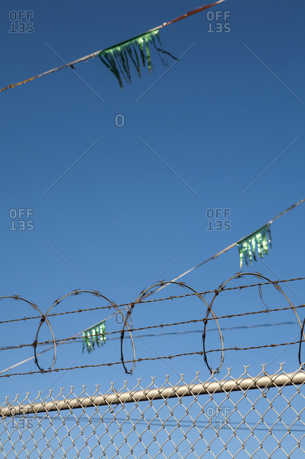 Metal fence,  barbed wire, razor wire and glittery green streamers