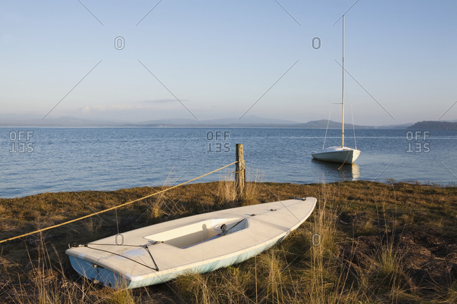 Small boats on the coast, beached on sand and moored in water