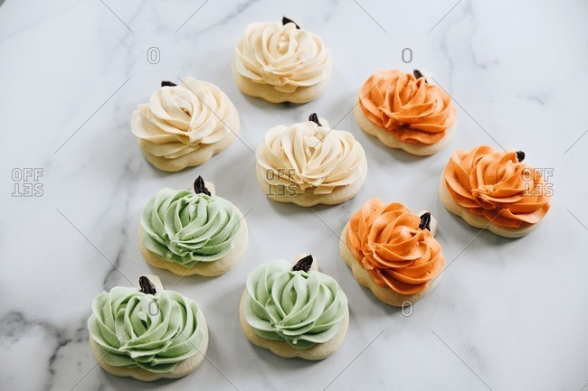 Pumpkin shaped sugar cookies with icing on a marble surface