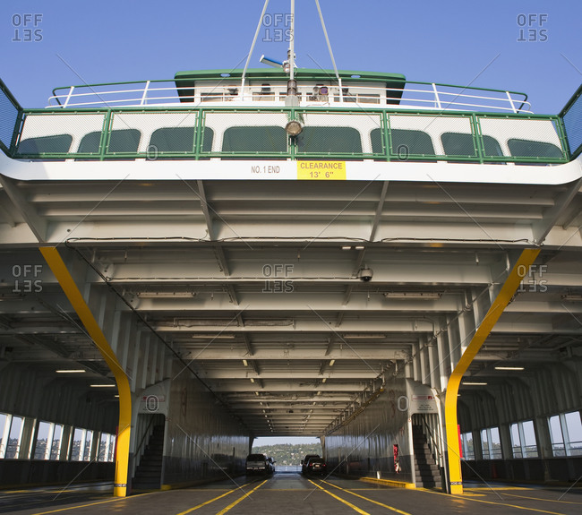 Car ferry on the water, car deck and upper deck, two cars and spaces