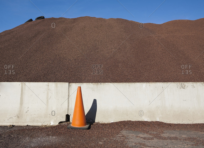 Heap of sand or gravel and orange safety cone