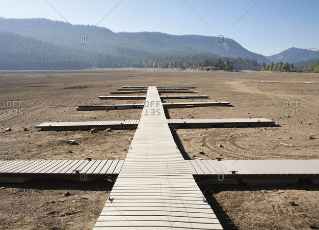 Planks laid out as walkways, jetties on flat dry desert soil, open space.