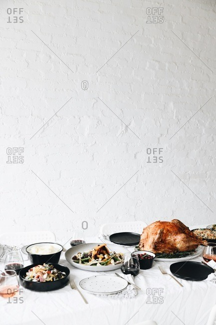 Traditional Thanksgiving dinner food served on a table in front of white texture wall