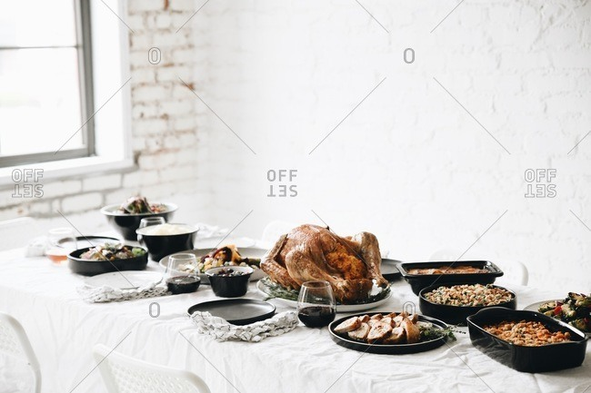 Roasted turkey and traditional Thanksgiving dinner side dishes served on a table in front of white texture wall