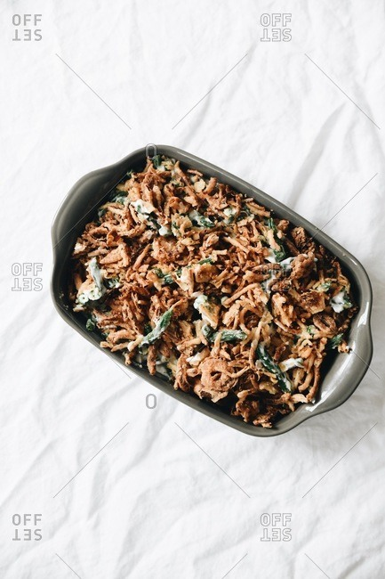 Overhead view of green bean casserole on white linen tablecloth