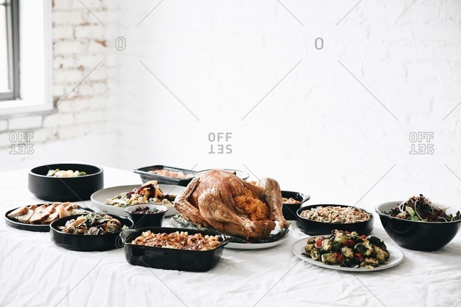 Traditional Thanksgiving dinner food served for a gathering on a table in front of white wall