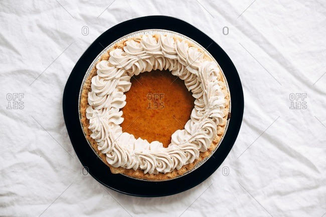 A whole pumpkin pie for Thanksgiving dessert on white linen tablecloth