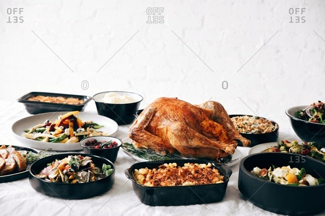 A traditional Thanksgiving dinner served on a table in front of white texture wall