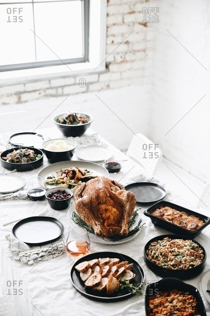 Elevated view over a traditional Thanksgiving dinner served on a table in front of a window