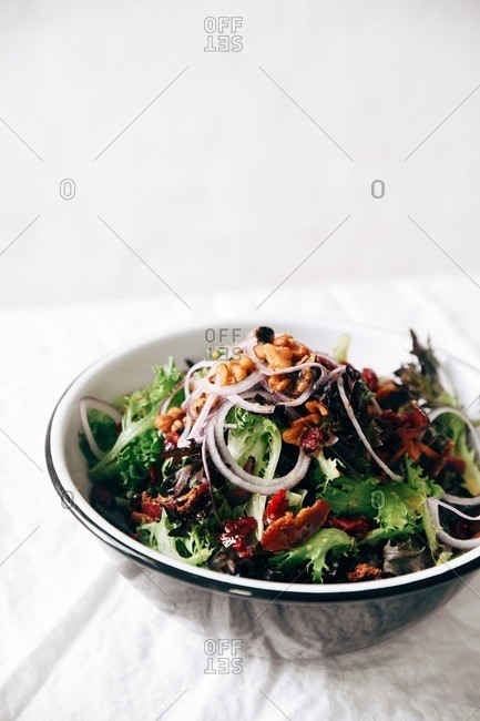 A large salad on table with white linen tablecloth