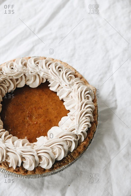 Overhead view of a whole pumpkin pie for a holiday dessert on white linen tablecloth