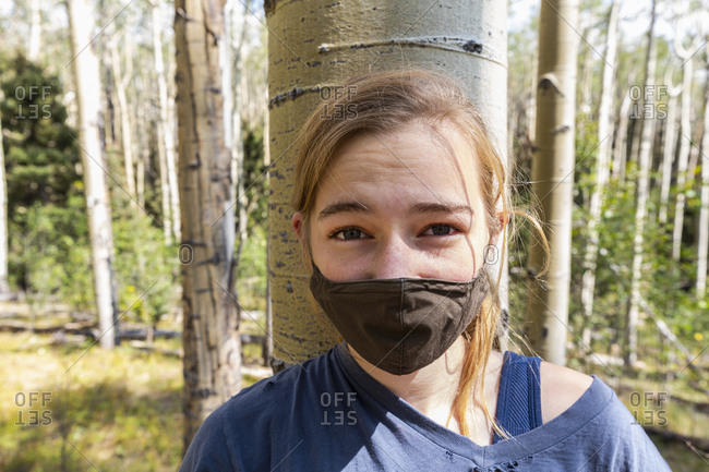 Teenage girl wearing COVID-19 mask in forest of Aspen trees