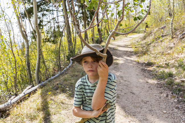 7 year old boy holding broken branch in forest of Aspen trees