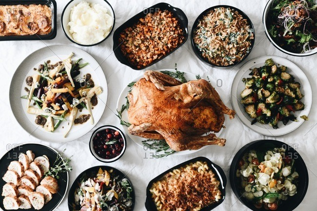 Top view of traditional Thanksgiving dinner food served on a table in front of a window