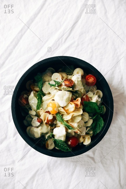 Pasta salad dish with vegetables and dressing on white linen tablecloth