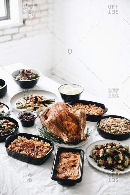 Holiday dinner with turkey and side dishes served on a table with white tablecloth
