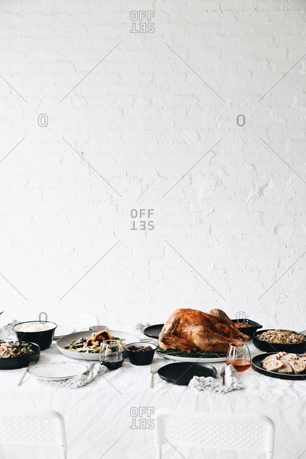 Thanksgiving feast served on a table in front of white texture wall