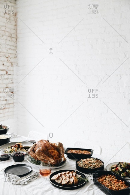 Thanksgiving feast for gathering served on a table in front of white texture wall