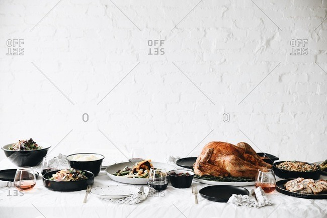 Thanksgiving turkey and side dishes served on a table in front of white texture wall