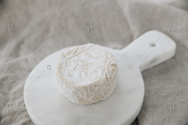 Soft white bloomy rind cheese wheel on marble