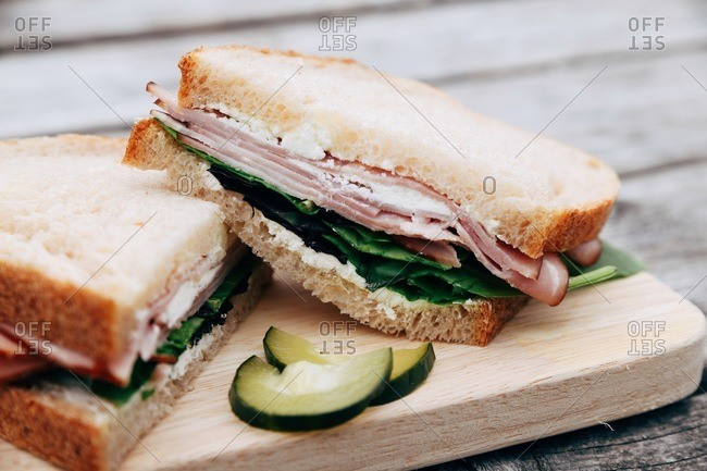 A ham and cheese sandwich with lettuce and pickles