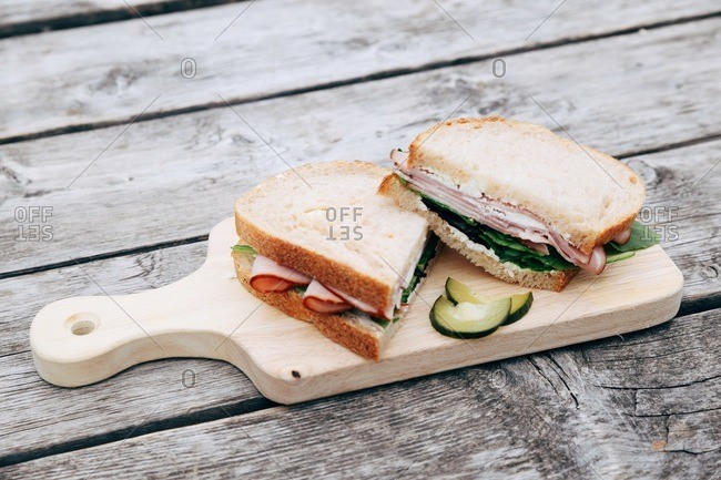 Ham and cheese sandwich with lettuce and pickles on a wooden board