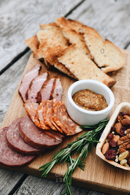 Meat board served on rustic wooden table