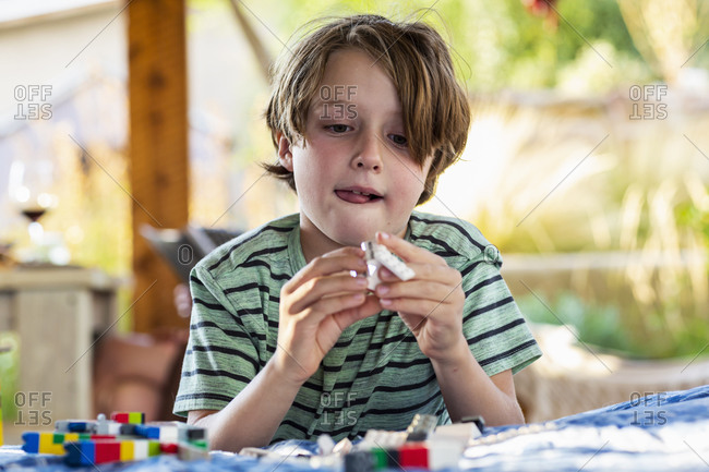 7 year old boy playing with building blocks on a terrace