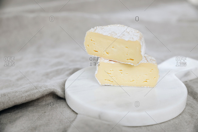 Soft white bloomy rind cheese wheel cut and stacked on marble